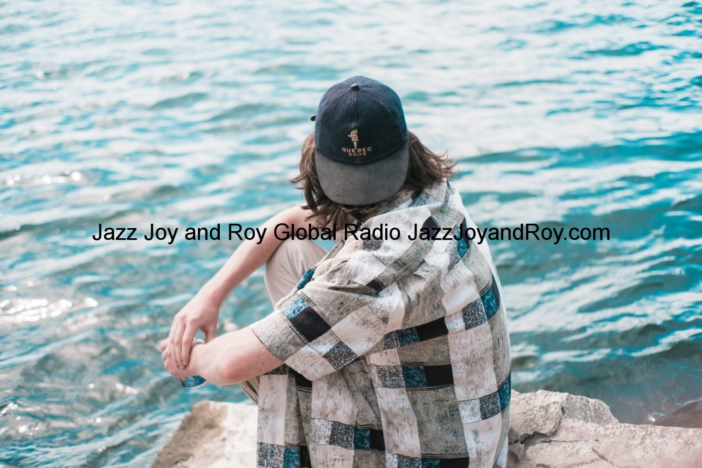 man in black cap and plaid shirt sitting on rock near body of water during daytime